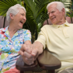Older couple smiling and holding hands